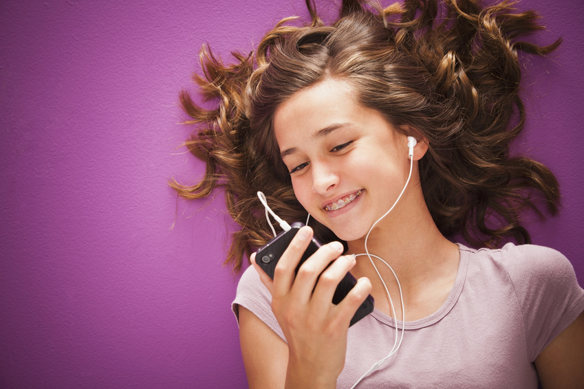 Caucasian teenager listening to music on mp3 player